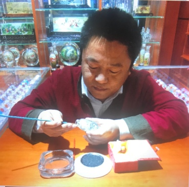 This is a famous Chinese artist who is known for painting tiny intricate designs inside bottles. He sell them at the market and will customize them w names if you want. I will go back and get one soon. He's amazing to watch.